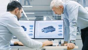 Zwei Maschinenbauingenieure konstruieren eine Montageanlage am Computer.