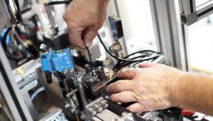 Maschinenbau Saarland – Ein Industriearbeiter befestigt ein Bauteil in einer Montageanlage
